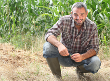 Farmer kneeling in field, happy about IL Ag Invest program